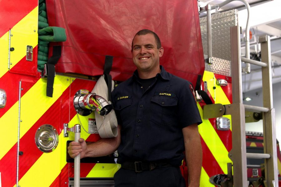 Fire+captain+and+paramedic+Ethan+Carver+stands+on+the+back+of+one+of+the+station%27s+fire+engines.+Carver+trained+at+the+TEEX+Brayton+Fire+Training+Field.