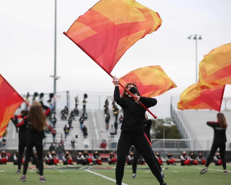 Senior Elise Bell spins her flag before she tosses the flag in the air. Bell is the captain of the color guard and was nominated for Homecoming Queen.
