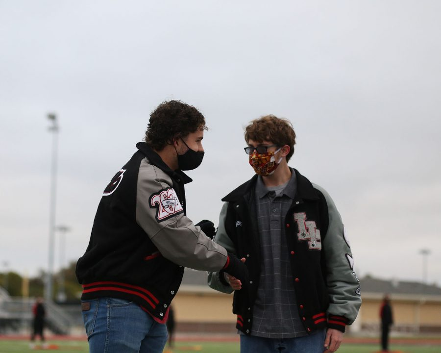 Senior Homecoming King nominees Sam Clay and JR Frazier shake hands as they wait for announcement of Homecoming King awards. Homecoming King and Queen will be announced during half-time at the game.