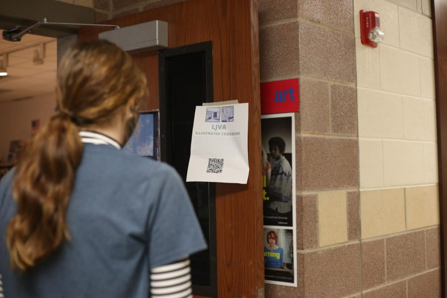 Student looks at LJVA's flyer about the cookbook. LJVA encourages students to submit recipes.