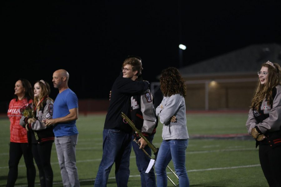 Senior Landon Snow hugs his parents after his name was called for senior recognition at half time. Snow is the section leader for the trombone.