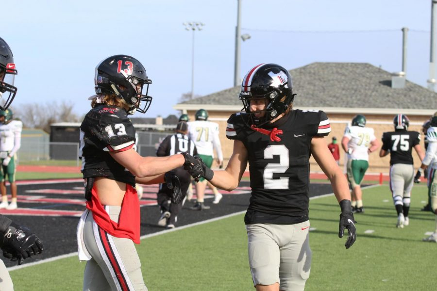Sophomore Jaxson Lavender and senior Luke Mayfield shake hands after Mayfield scored a touchdown. The Leopards continued their undefeated streak with winning this game.