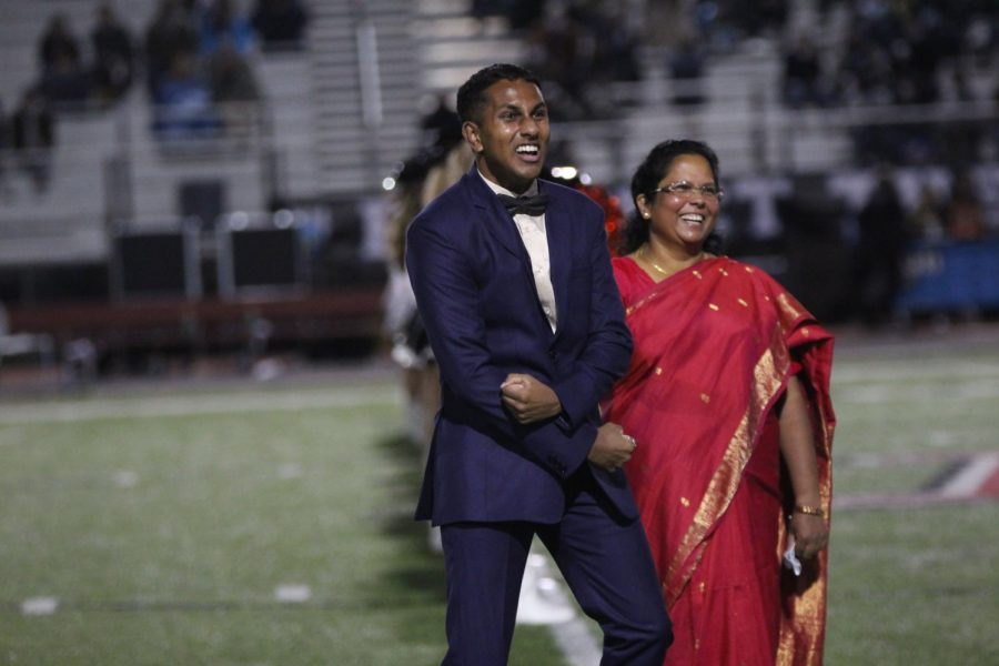 Seniors Peter Godipelly walks out with his mom. Godipelly was voted homecoming king and most spirited male this year.
