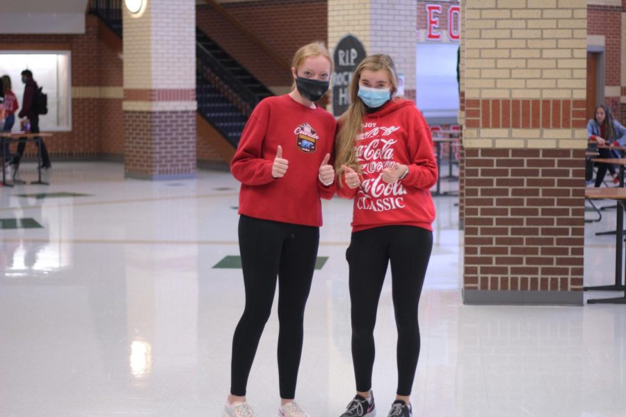 Juniors Madison Cinek and Bailey Bradshaw wear red sweatshirts for red out. Bradshaw plays softball for the high school.