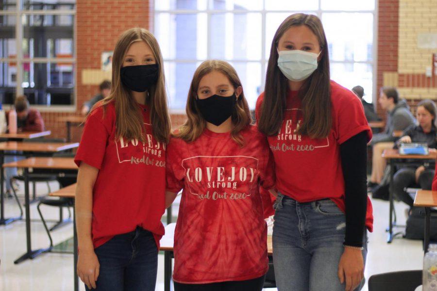Freshmen Avery Hammett, Grace Johnson, and Addison Vondersarr wear this year's homecoming shirts. Band sold these shirts to the community.