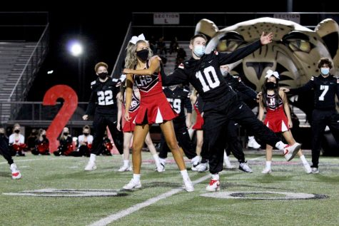 Seniors Elle Brumley and Ralph Rucker dance together in the cheer and football senior dance. Brumley is the captain of the cheer team.