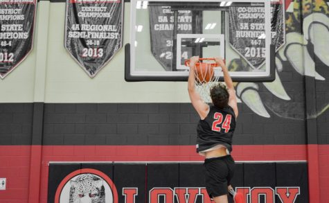 Senior Carson Holden dunks a basketball. Holden plays shooting guard for the Leopards.