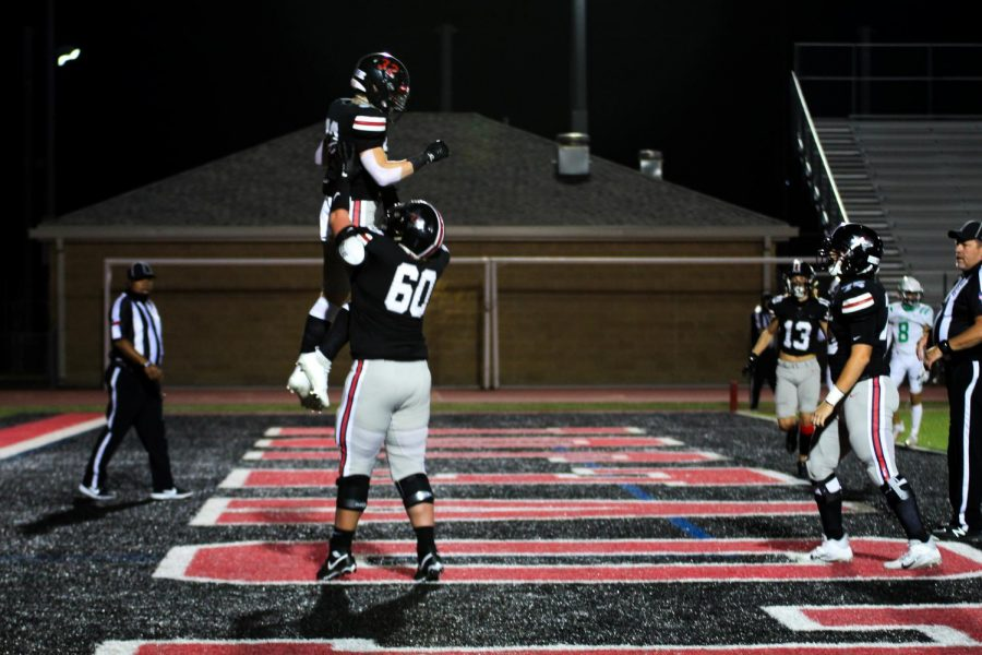 Freshman Matthew Mainord and senior Trent Robinson jump in the air after making a touchdown. This touchdown put the Leopards at 52 points.