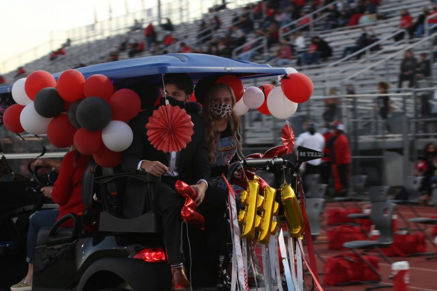 Homecoming king and queen nominees Emma Boland and Sam Clay ride in their golf cart. The king and queen nominees all rode in on decorated golf carts.
