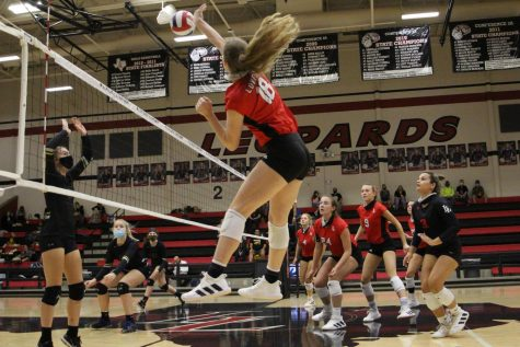 Junior Megan Diercks hits the ball for the return. The return wins the Leopards the point.