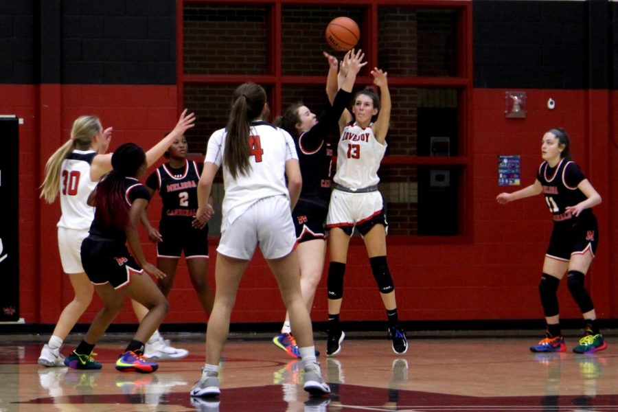 Senior Katie Dolberry makes an overhead pass to sophomore Sam Basson on her end of the court. Basson receives the pass and sets up for another pass.