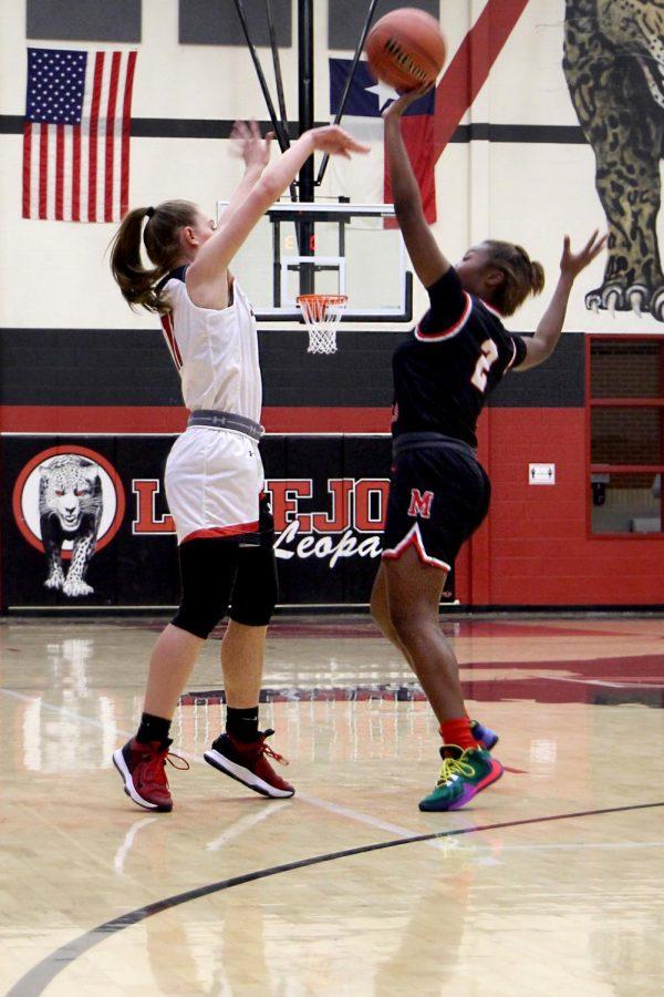 Sophomore Chloe Schaeffer makes a high pass avoiding the defender. The Leopards score a basket following the pass.