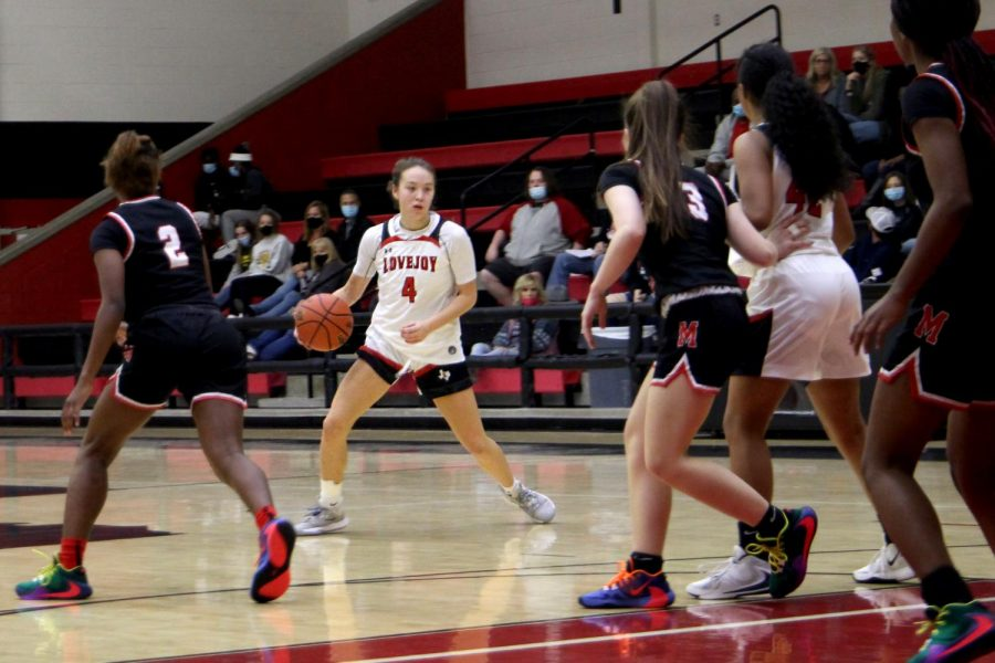 Sophomore Sam Basson crosses over the juke the defender. Basson drives toward the basket to attempt a shot.