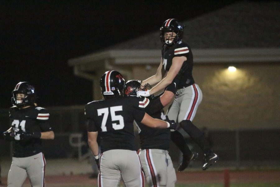 Senior Trent Robinson lifts Senior Reid Westervelt after Westervelt scored a touchdown. Westervelt is a receiver for the football team.