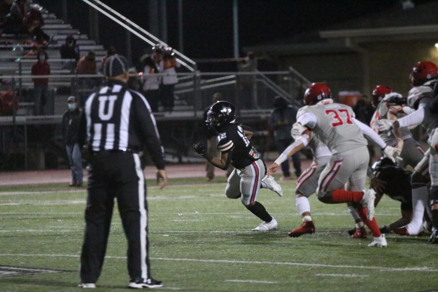 Junior Noah Naidoo attempts to make a touchdown. Naidoo is a running back for the Leopards.