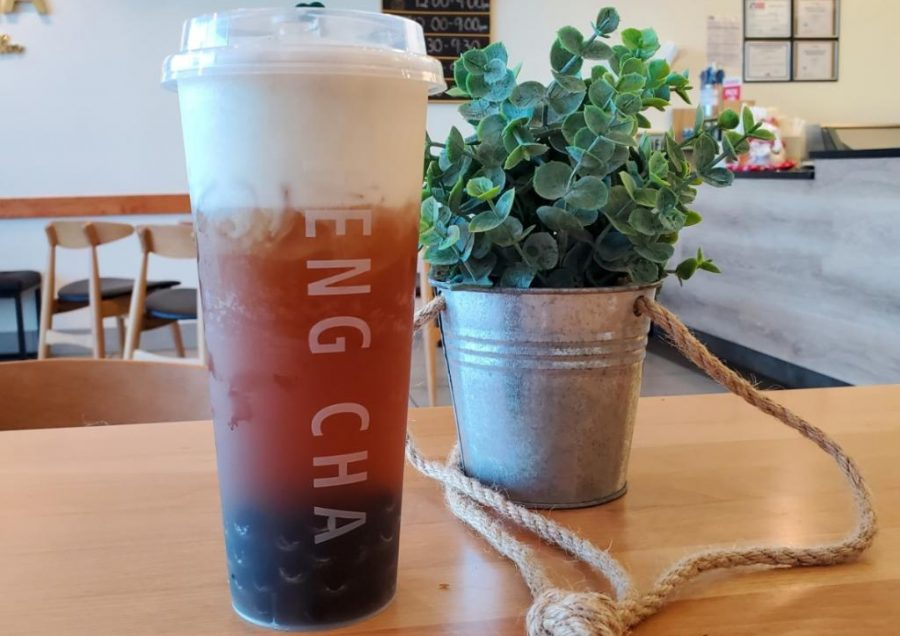 Feng Cha's earl grey milk tea is placed next to a simple house-plant in a tin pail, which can be found on each table. The plants add to the aesthetic of the shop.