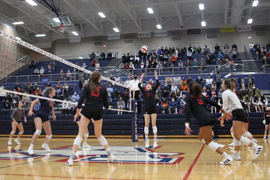 Junior Averi Carlson sets the ball for Cecily Bramschreiber to make the return. The Leopards won the point after a long volly following the return.