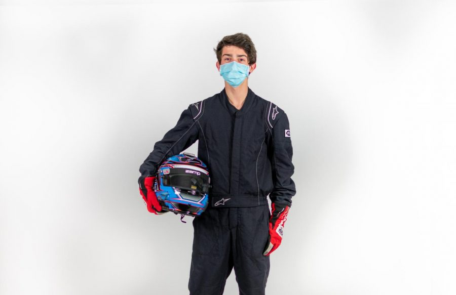 Junior Aidan Meek stands in full racing gear with his helmet. Meek plans to eventually buy his own racing car.