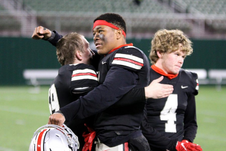 Senior linebacker Shawn Robertson and senior defensive lineman Garrison Alling hug after the loss to Aledo. The team played the last three of their four playoff games at Globe Life Park in Arlington.