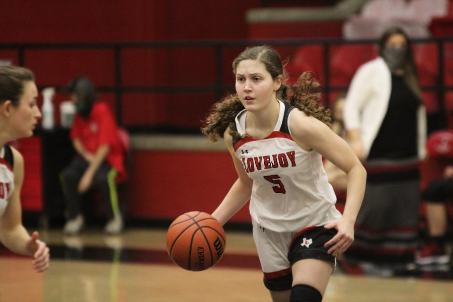 Senior Maddie Clancy dribbles down the court toward her teammates. Clancy scored two points and had one rebound for the leopards.
