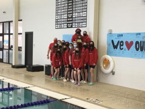 Girls varsity swim team captain Amelia Poulton holds the district championship plaque  after the team won the meet. This is the second year in a row that the team has won the district meet.