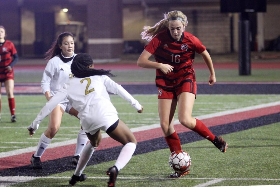 Sophomore left outside defender no. 16 Emmy Woods dribbles the ball around junior midfielder no. 2 Kenya Reynolds. The girls soccer team will play Wylie East away tomorrow.