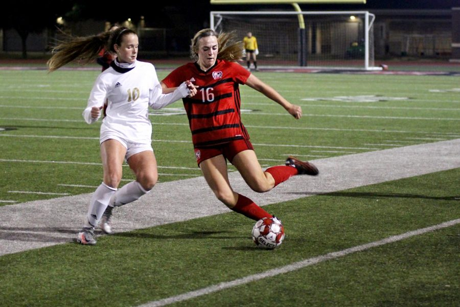 Sophomore left outside defender no. 16 Emmy Woods crosses the ball past sophomore midfielder no. 10 Kristen Sueltz. The Leopards tied the game in regulation play.