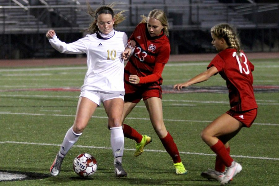 Junior outside forward no. 23 Avery Templin and senior attacking mid no. 13 Hannah Dunlap double team sophomore midfielder no. 10 Kristen Sueltz. Dunlap was one of the players to score a penalty kick.