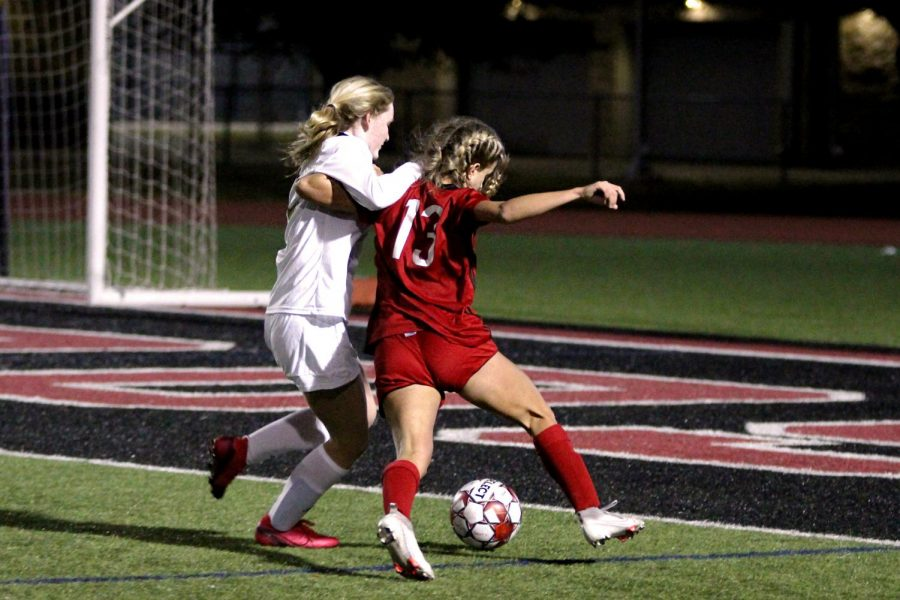Senior attacking midfielder no. 13 Hannah Dunlap goes around a Cougar defender. Dunlap played all eighty minutes of the game.