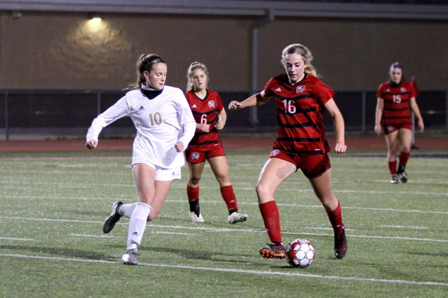 Sophomore left outside defender no. 16 Emmy Woods dribbles the ball past sophomore midfielder no. 10 Kristen Sueltz. Woods plays for the Dallas Texas soccer club.