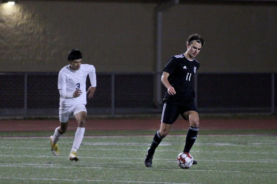 Senior defender no. 11 Brandon White dribbles the ball. The team won this game with a final score of 3-0.