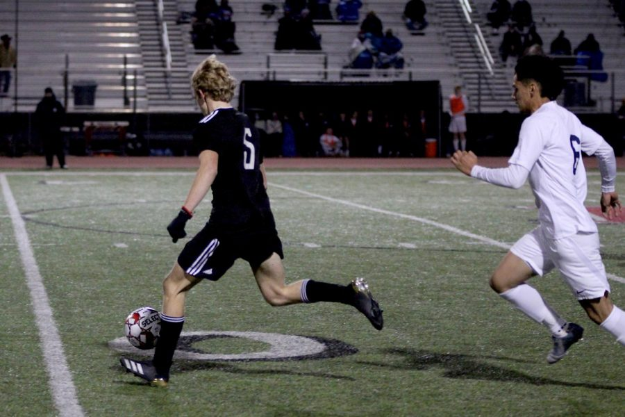 Sophomore forward no. 5 Caden Carlock runs with the ball past junior forward no. 6 Nathan Ferrel. Carlock scored one of the three goals of the game.