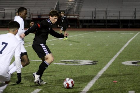 Senior forward no. 3 Michael Myers dribbles the ball out of Raider players. Myers scored two goals of the game.