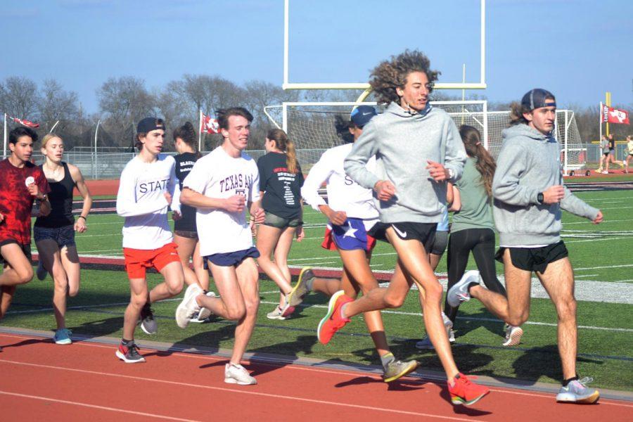 Freshmen Andrew Poulton, senior John Armstrong, junior Tate Barr, and senior Trevor Malik run their warm up mile. The track team has their first meet on Feb. 11 at the high school.
