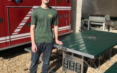 Sophomore Dawton Bruner stands next to the table he built and donated to the Lucas Fire Department. Bruner received his Eagle Scout for the project.