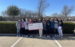 Girls basketball players hold the check made out to Cornerstone Ranch by the basketball booster clubs. The check is for a sum of $8,043.41.