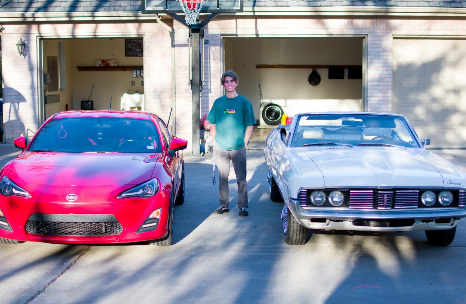Junior Brendan burner stands next to his white 1969 Mercury Cougar Convertible and his red 2013 Scion FR-S. He bought the Mercury Cougar from his grandfather and has been working to get the car back together and working again.