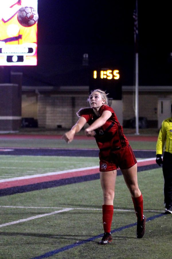 Sophomore left outside defender no. 16 Emmy Wood throws the ball towards the goal. The team is currently ranked third in district.