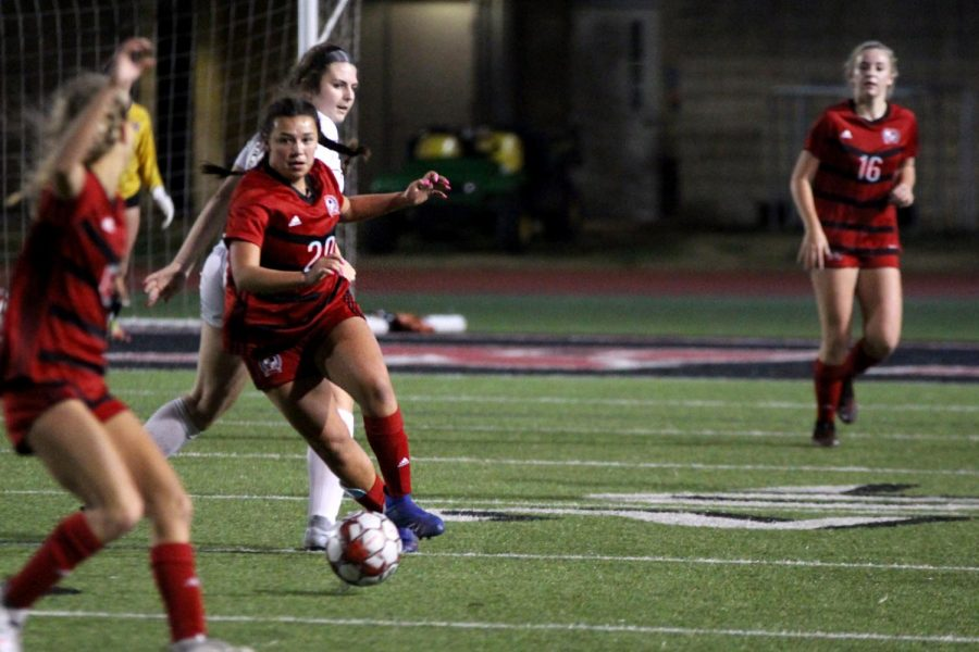 Senior defender no. 20 Natalie Reyna dribbles the ball towards the 30-yard line. The team is now at 2-1 for the district season.