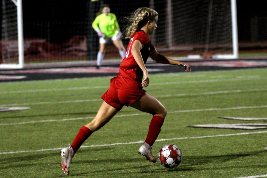 Senior attacking midfielder no. 13 Hannah Dunlap dribbles the ball towards the center of the field to attempt to score a goal. Dunlap scored the first goal of the game.