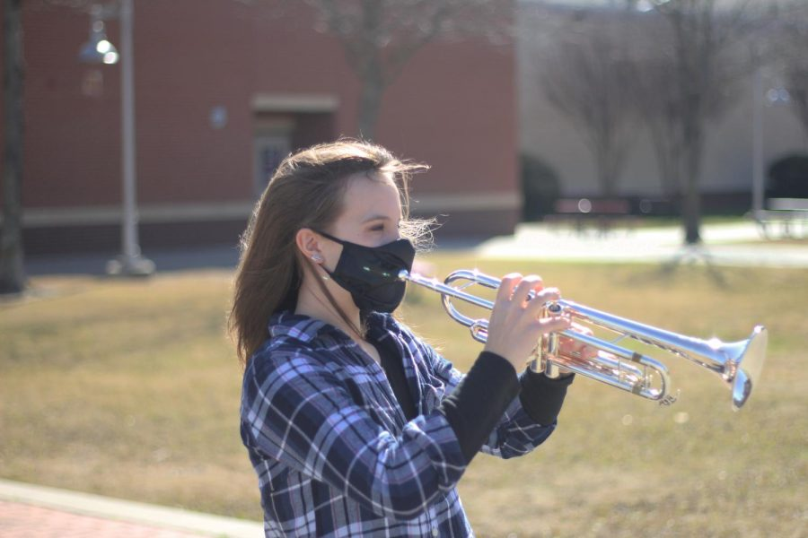 Freshman Reagan Wagner practices playing her trumpet in the school courtyard. Wagner plays in the Wind Symphony, the highest band at the high school.