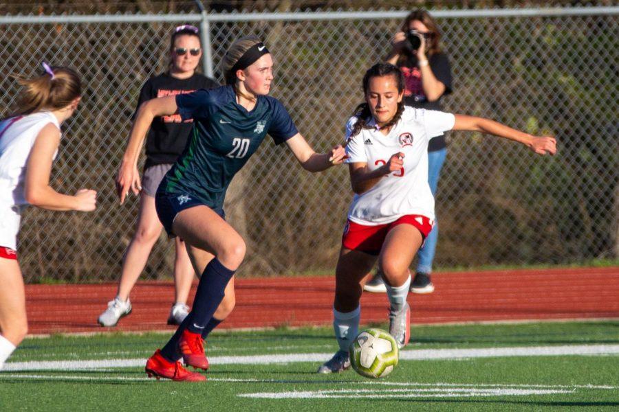 Sophomore holding mid no. 25 Natalia Duran de La Vega runs the ball past junior defensive midfielder no. 20 Zoe Calyer. The Leopards finished their season second in district.