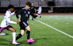 Senior outside midfielder no. 14 Gavin Moore dribbles the ball. Moore is committed to play for Dallas Baptist University in the fall.