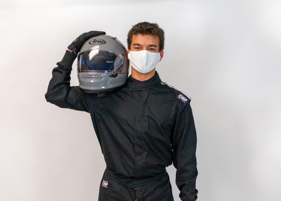 Sophomore Alex Williams stands in full racing uniform, holding his helmet. Alex received a 100cc go-kart for his birthday which he now uses to race competitively.