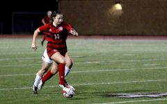 Freshmen outside forward no. 14 Taylor Personn dribbles the ball past the 40 yard line. Person started the game as a forward.