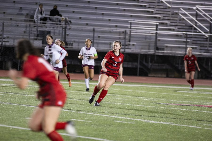 Senior midfielder no. 3 Katie Welch kicks the ball towards the goal. Welch is one of the team captains.