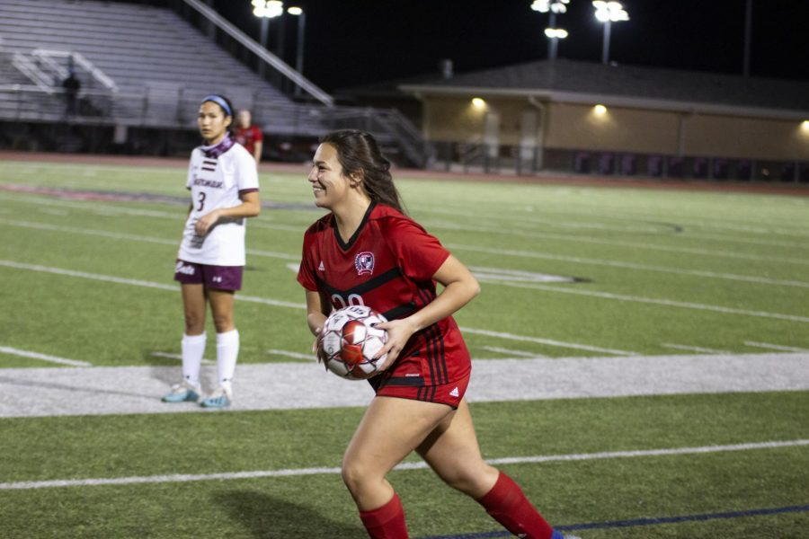 Senior defender no. 20 Natalie Reyna smiles as she throws the ball back into play. The Leopards had a lead of 3-0 in the second half of the game.