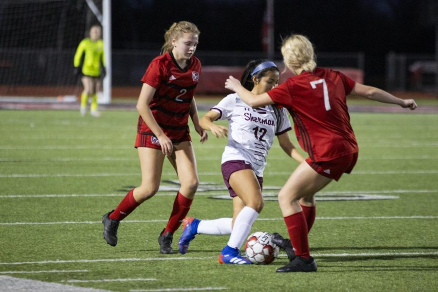 Junior forward no. 7 Tatum Chester blocks the ball from senior midfielder no. 12 Lizbeth Sanchez. The team is now 7-1-2 in the district season.