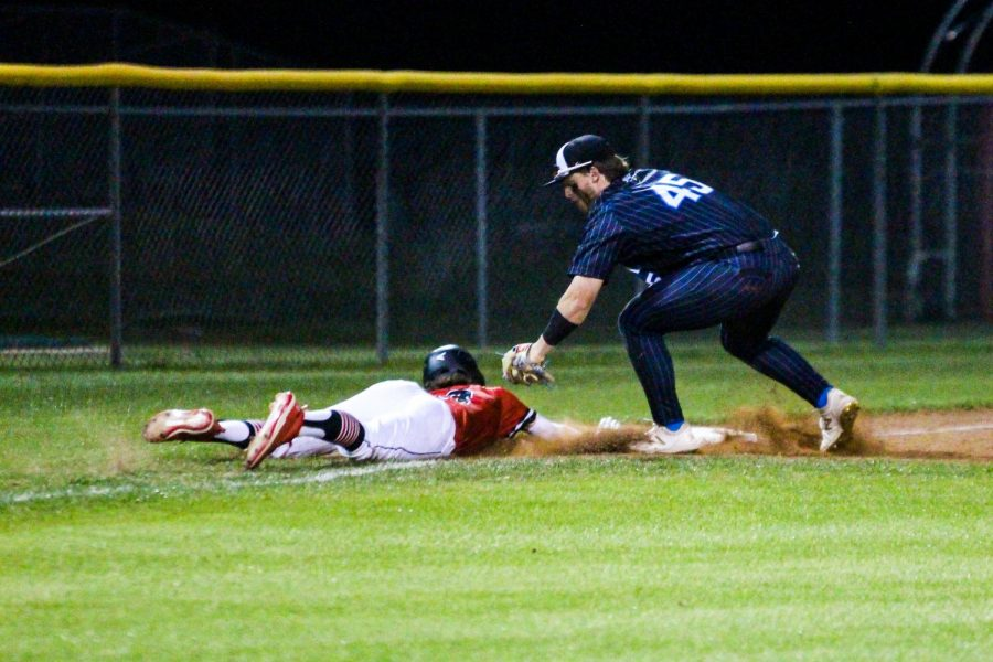 Sophomore center fielder no. 13 Aidan Smith dives back to third base after a hit by senior catcher no. 14 Ralph Rucker. Smith was able to get in under the tag of Rockhill's senior third baseman no. 45 Josh Livingston.