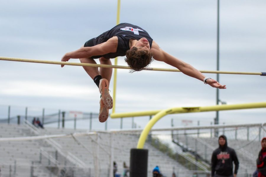 Freshmen high jumper Colston Adamson jumps over the bar. Adamson cleared the bar at 6'4 tying the school record and winning the event.